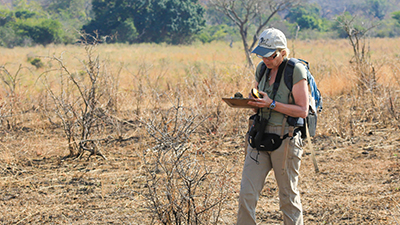Volunteer analyzing data while hiking in the field