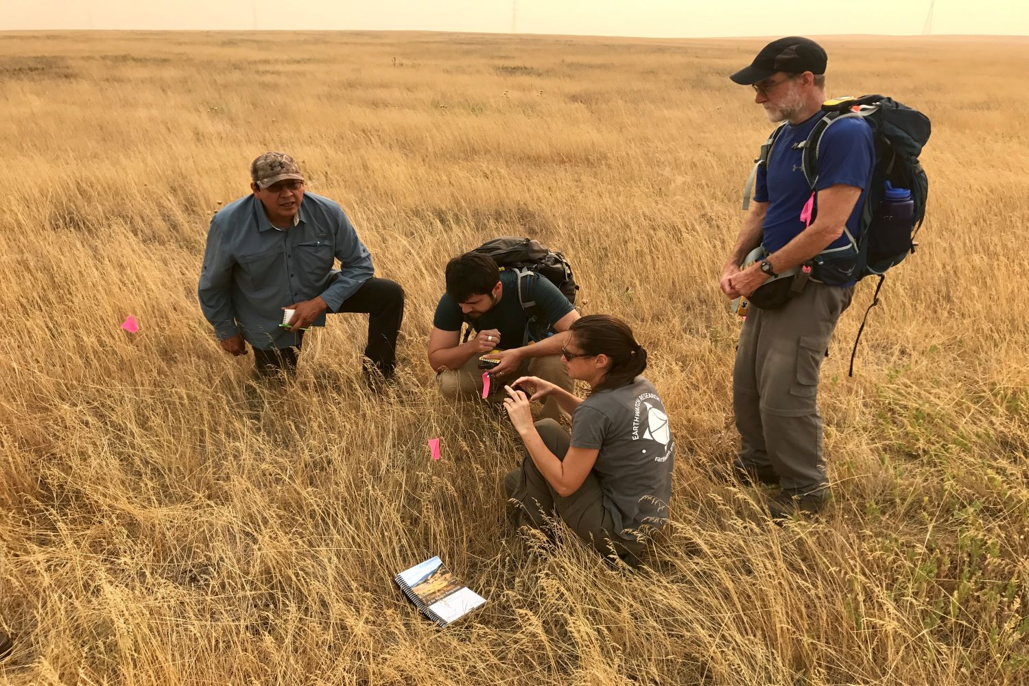 Elliot Fox, senior field technician, teaches volunteers about native and non-native grasses and bison habitat. (Photo: Stephen Hart)