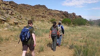 Earthwatch volunteers hike to survey vegetation and wildlife