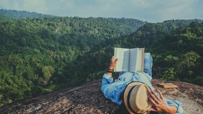 man reading one of the best science books - on a mountaintop as nature intended