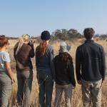 Earthwatch volunteers observe rhinos in the distance (C) Lynne MacTavish